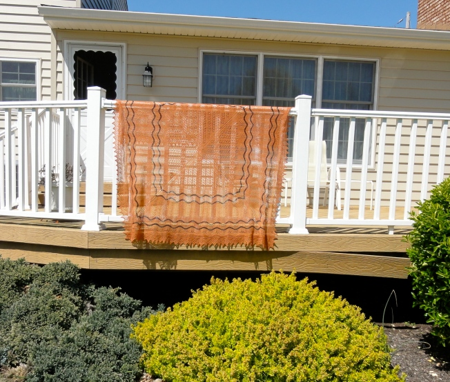 Calico Cat's Paw Square Shawl on the deck railing