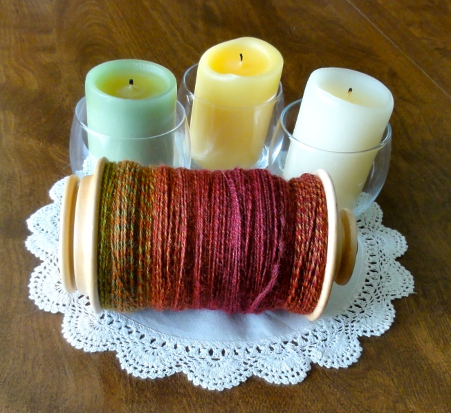 A bobbin full of 4-ply handspun BFL