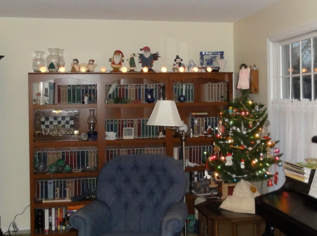 Lights, Santas, and snow people on top the the bookcase, and an angel on top of the tree