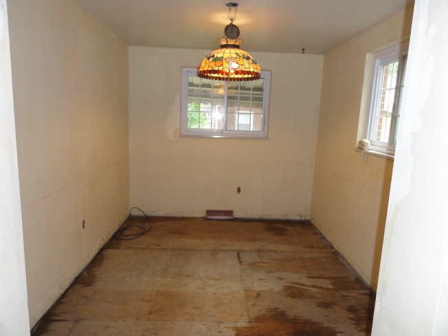 The breakfast nook sans flooring. The wet spots are from the cleanup.
