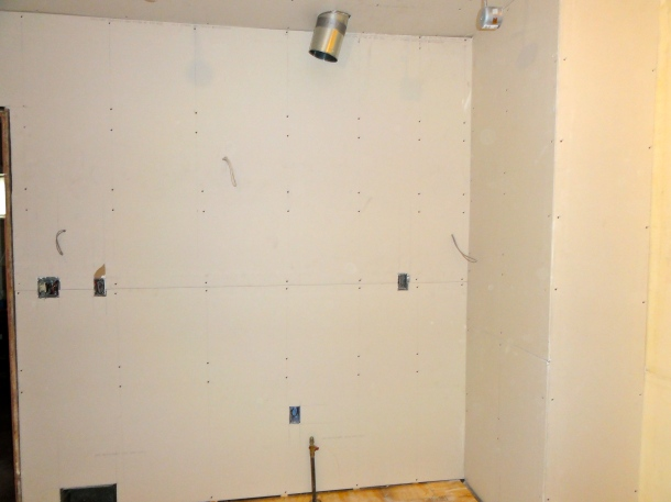 Drywall on the interior wall where the stove will be
