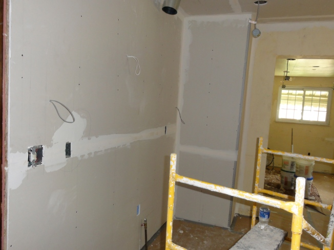 Drywall behind the stove, partially finished
